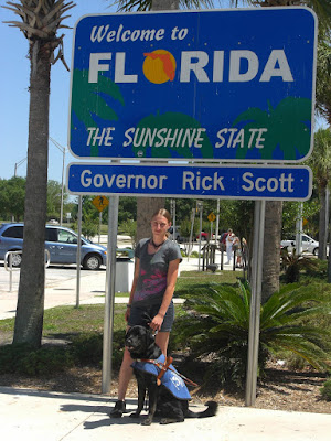 Picture of Rudy & I beside the FL state sign (Rudy is in coat/harness)