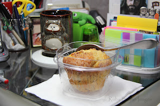 Eating muffin at workstation.