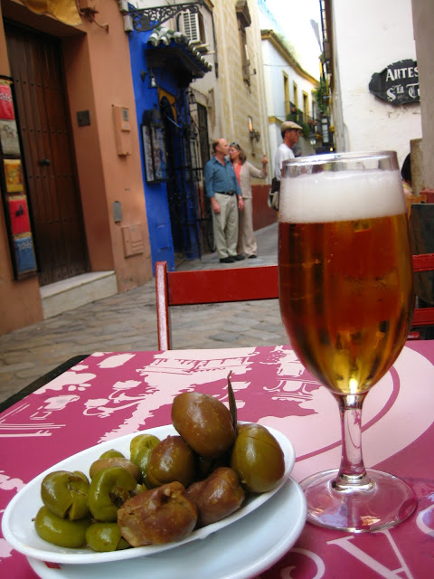 Bowl of olives and beer in Seville, Spain street cafe.