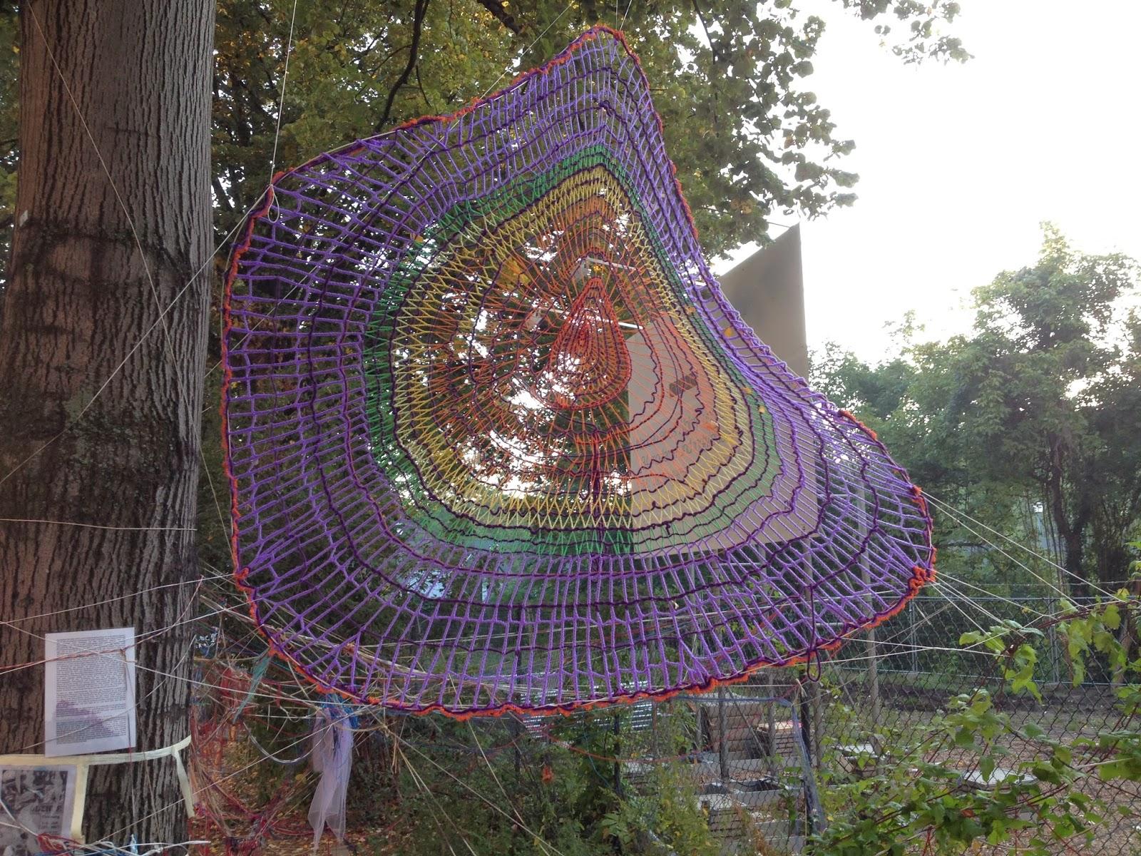 Buntes Spinnennetz aus Strickwolle im Baum