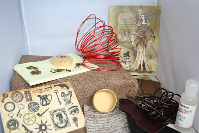 a photo of the contents of the crafty creatives march 2013 box. this includes an art card by Britta van den Boom, a decoupage trinket box kit, 3 metres of brown leather cord, pipe spacer beads, bottle of crackle glaze, metallic transfer foils, bundle of leather scraps, reel of wire, bulb and clock charms, lock clasps, watch parts, brown tweed fabric with metallic copper twist.