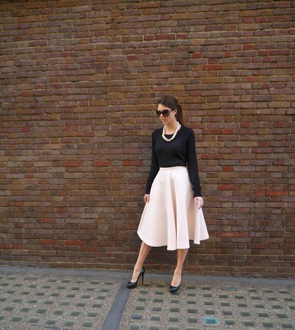 Pale pink midi skirt and black cashmere sweater in Mayfair