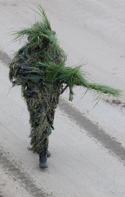 soldado camuflado com plantas arbusto