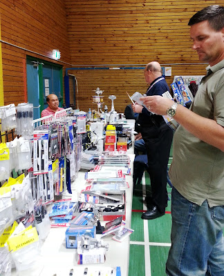Two men shopping at a stall at a scale model show.
