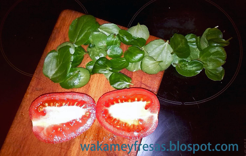 berros y tomates en la tabla de cortar