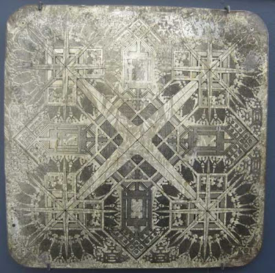 Square silver board with decorative pattern kind of like an ornate parcheesi board