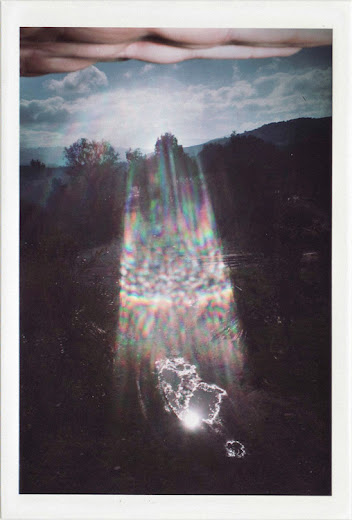 dirty photos - time - cretan landscape photo of lens flare and hand