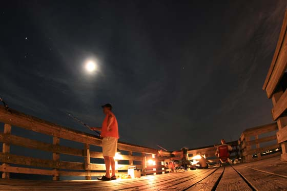 Fishing at night under the moon and stars on a pier in Isle of Palms, South Carolina.