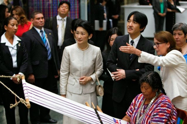 Japan's Prince Akishino and his wife Princess Kiko listen to a translator as they stand next to a woman making a huipil (traditional Mayan blouse) during a visit to the Ixchel museum in Guatemala City,