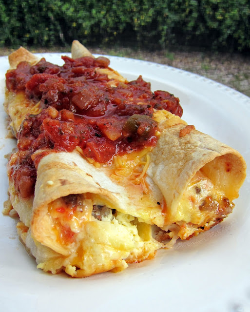 Southwestern Quichiladas Recipe - overnight breakfast enchiladas - tortillas stuffed with sausage, Rotel and cheese with an egg and half and half mixture poured over top - assemble the night before and pop in the oven for an easy breakfast! Top with salsa to kick it up a notch. Great for overnight guest or school morning breakfast.