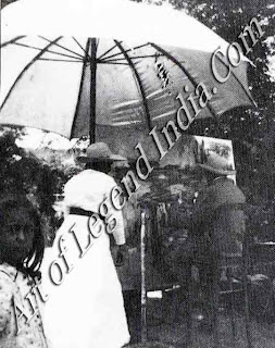 Monet at work Under a huge white parasol, Monet works on one of his waterlily paintings in the garden at Giverny. Beside him stands his step-daughter Blanche Hoschede-Monet, ready to change the canvas on his easel.