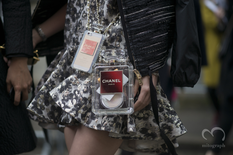 woman carrying Chanel no5 clutch bag and iphone case during Paris Fashion Week 2014 Fall WInter Season