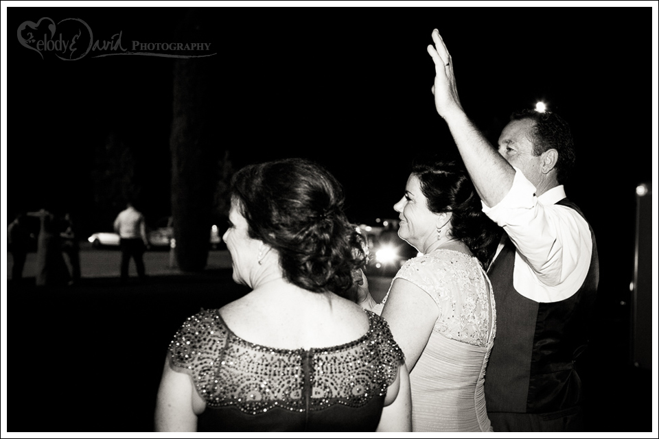 Parents waving to the bride and groom.