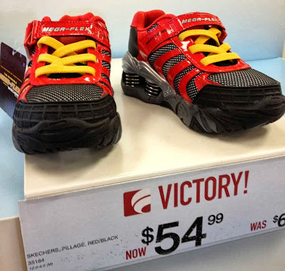 Shiny red kids' running shoes with yellow laces, black soles