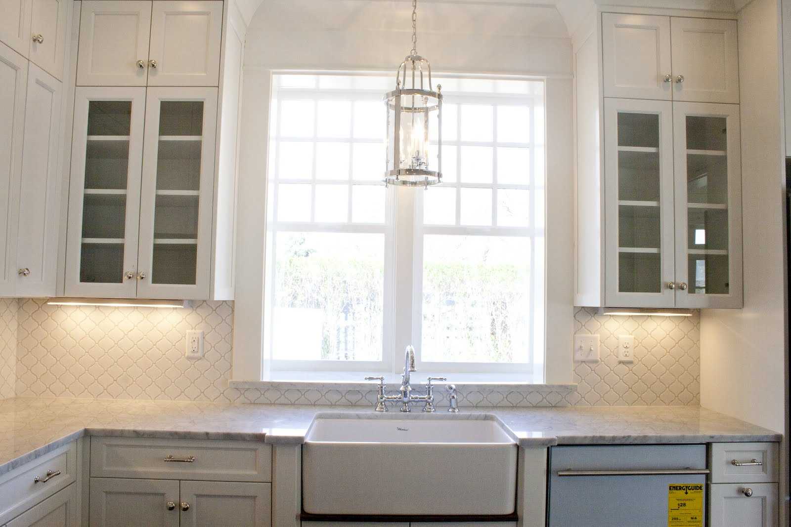 Loving the white kitchen tiek built homes for Over the kitchen sink pendant lights