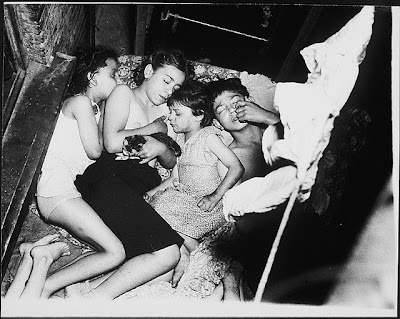 photograph of children sleeping outside in the summer on a fire escape