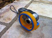 A câmera com a a base e um adaptador na frente da lente, que permite que câmeras com lente exposta possa se movimentar dentro dessa bolsa.
