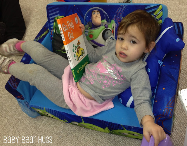 toddler laying on a small couch reading a Dr. Suess book