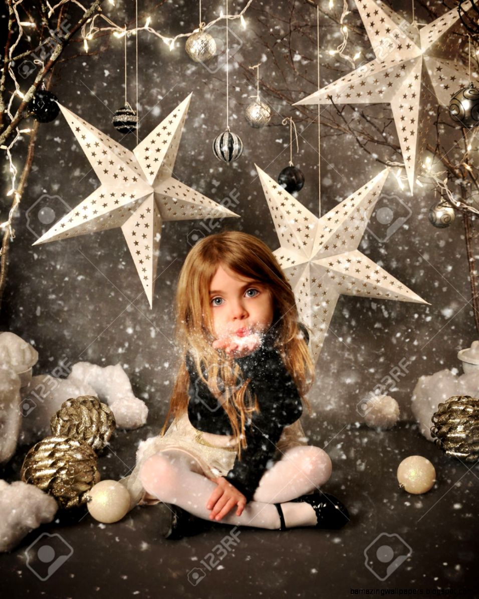 A Little Child Is Sitting On A Winter Wonderland Backdrop With