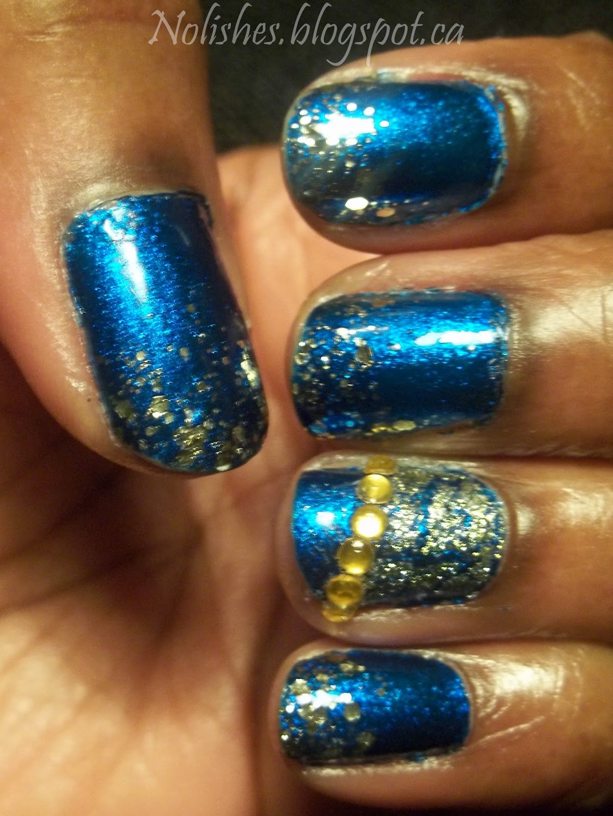 Ornate manicure featuring shimmery deep turquoise base polish, and a gold glitter gradient starting from the tips. Ring finger accent nail is partially covered with gold crackle topcoat, and a row of amber coloured nail art rhinestones