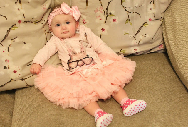 baby wearing pink tutu, pink top with bunny wearing glasses, pink bow headband and pink star converse style daps