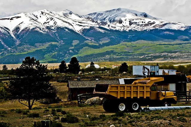 Snow capped mountains behind a parked dump truck outside of Leadville, Colorado.