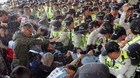image of large group of police on right, pepper spraying protesters on left of frame