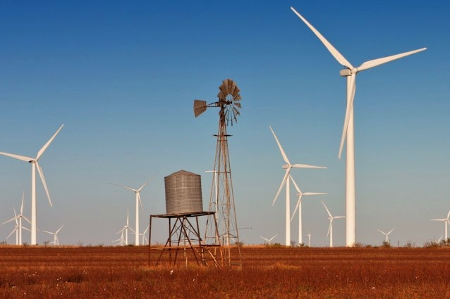 A vintage windmill in a cotton field in West Texas, with modern wind turbines in the background. (Credit: Shutterstock) Click to enlarge.
