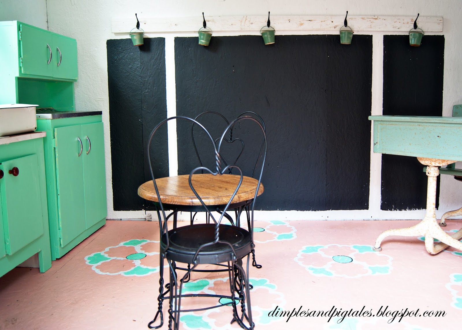 Playhouse with mint green cabinets, coral painted floor, chalkboard wainscoting and vintage accessories.