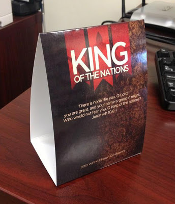 "dark-colored promotional table tent on a table, featuring ""King of the Nations"", printed by GotPrint.com"