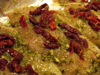 Uncooked chicken topped with pesto and sundried tomatoes.