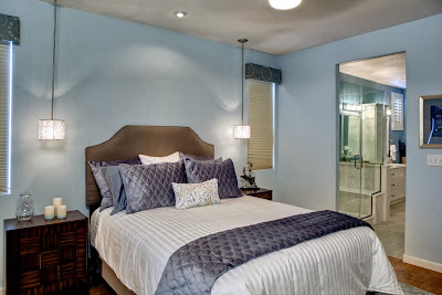 comfortable bed accompanied by stylish end tables and beautiful pendant lights