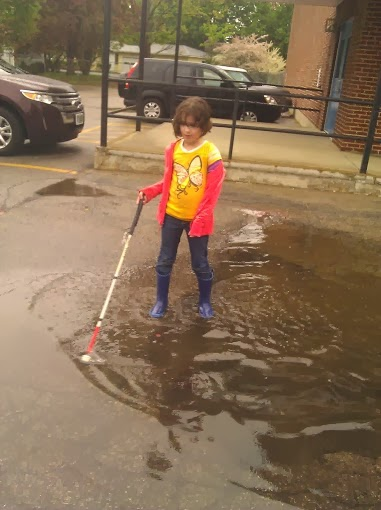 Girl in puddle, wearing rainboots with wet hair and white cane.