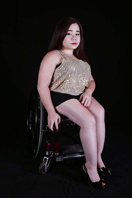 A picture of a young female with a gazing expression, wearing a sparkle gold tank top and a black skirt, sitting in a purple wheelchair, with a black background. Her legs are angled outside of the chair and a scar appears on the right side of her thigh.