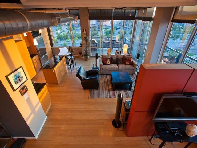Living room and the kitchen in Denver penthouse as seen from round staircase to the roof terrace