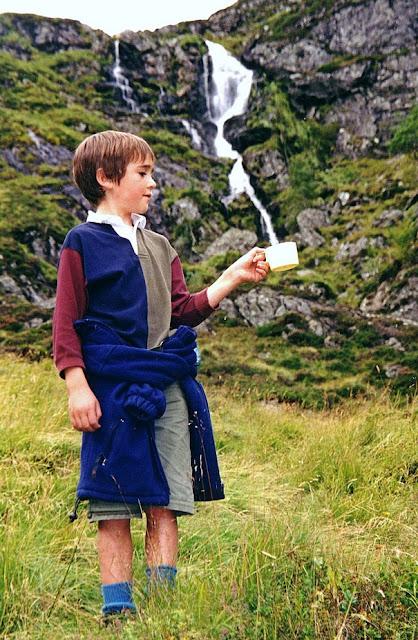 niño con una taza en el campo