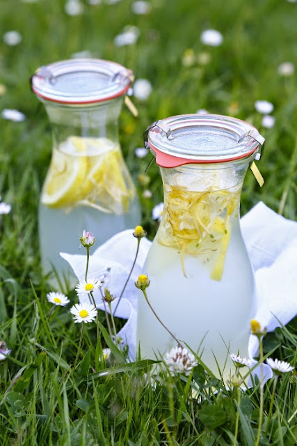 Two glass bottles filled with lemonade, in the grass
