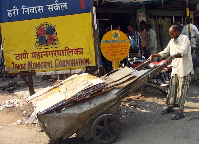 a cart loaded with cardboard and made of two wheels pulled by a man