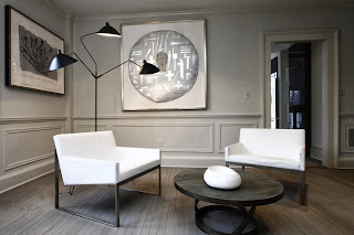 sitting room full of artistics contemporary chairs and table accompanied by unique silvery wall decoration
