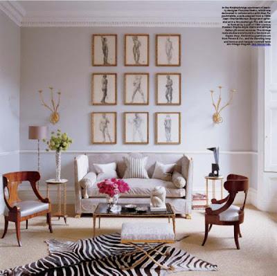 apliques dorados de pared en salon con alfombra de cebra y butacas de cerezo