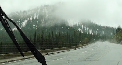 Windshield wiper clears rain to expose snow covered mountain