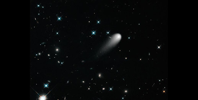 The sun-approaching Comet ISON floats against a seemingly infinite backdrop of numerous galaxies and a handful of foreground stars in this April 2013 composite image from the Hubble Telescope. Credit: Reuters/NASA, ESA, and the Hubble Heritage Team (STScI/AURA)