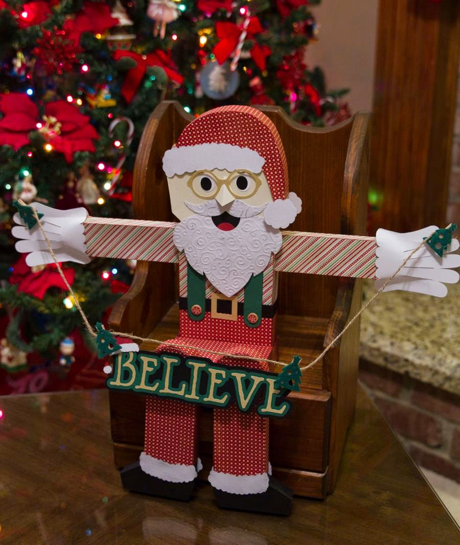 Scene of Santa sitting in little chair holding Believe sign next to Christmas Tree