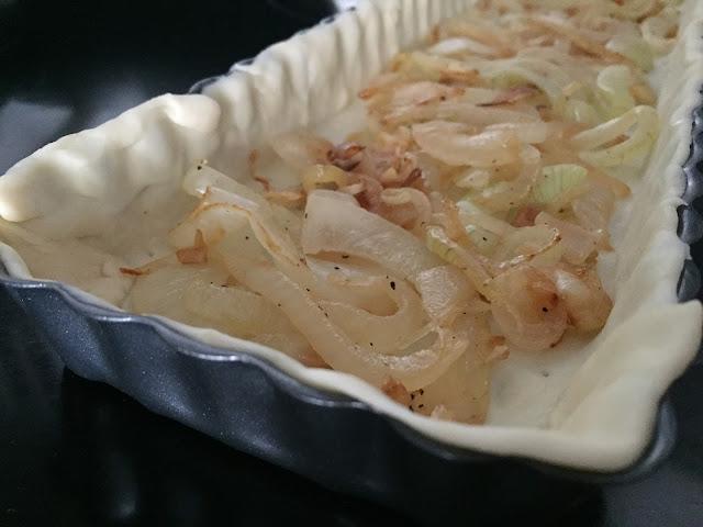 Hojaldre de sardinas y tomates. Extendiendo cebolla y ajo en el fondo.