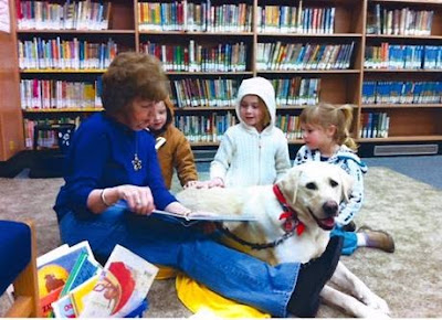 Carole and yellow Lab Olympic with audience of children