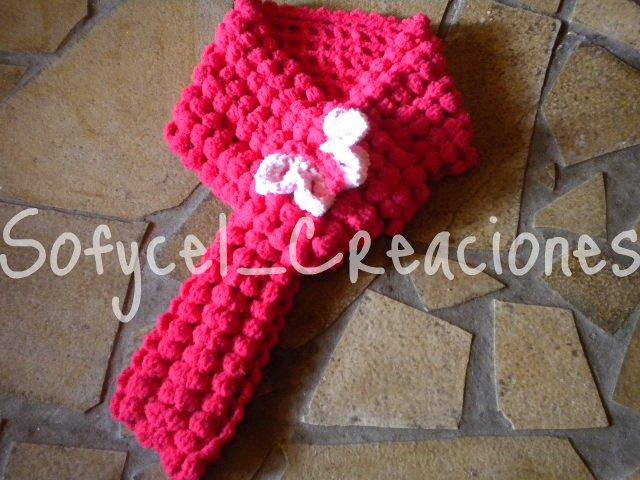 Una bonita bufanda para niña en color rojo, realizada con Nuvol de lanas Stop en crochet simulando a las lanas con pompones. Y de adorno una mariposa tejida