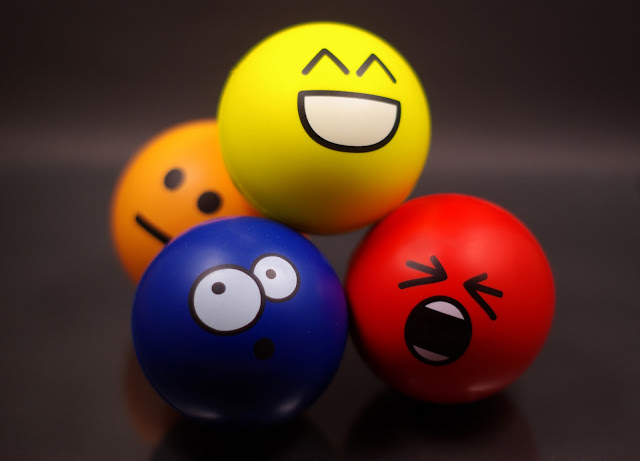Four bouncy balls painted with different emotions:  happiness, fright, apathy, and curiosity.
