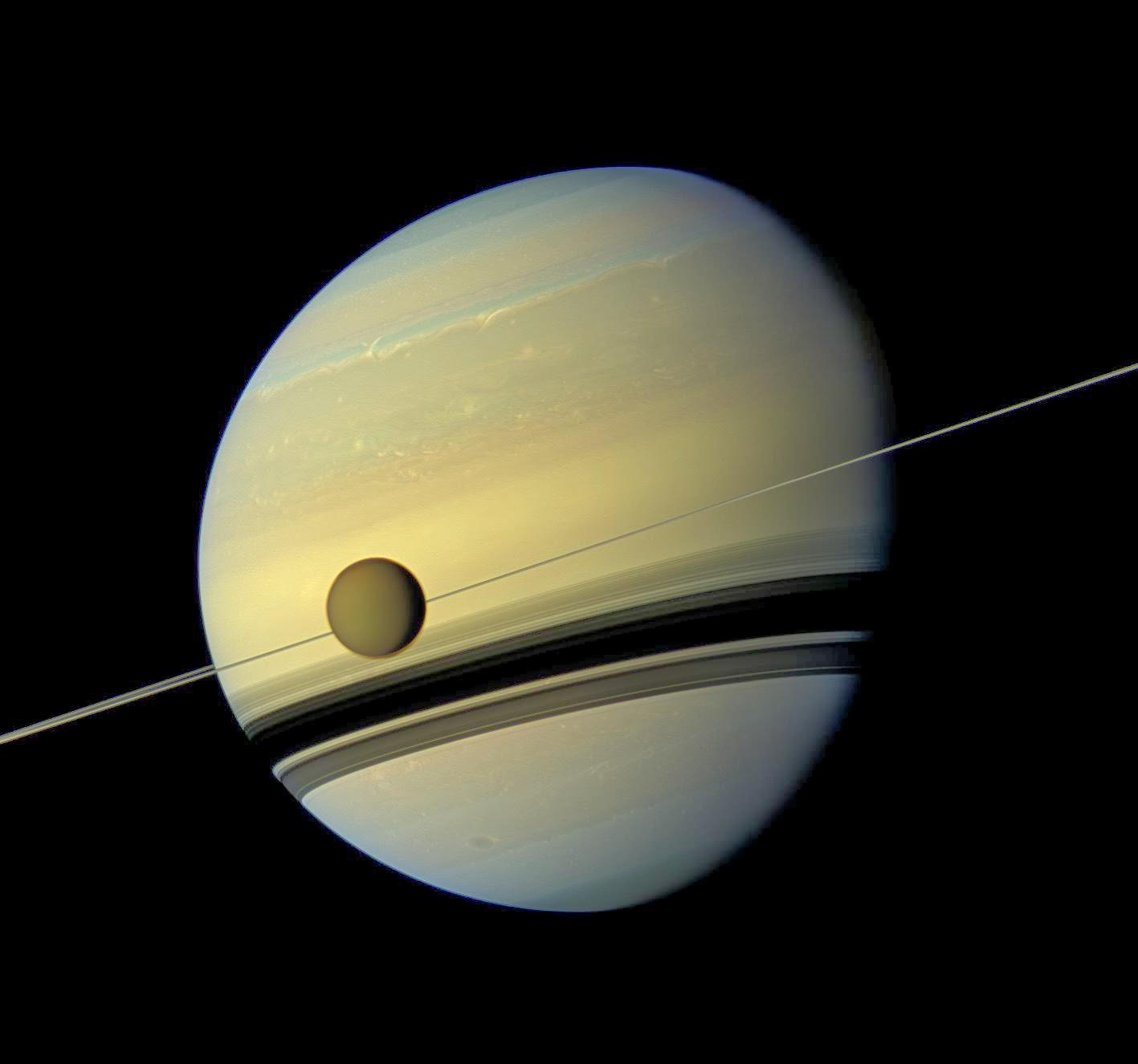 Титан на фоне Сатурна и его тонких колец