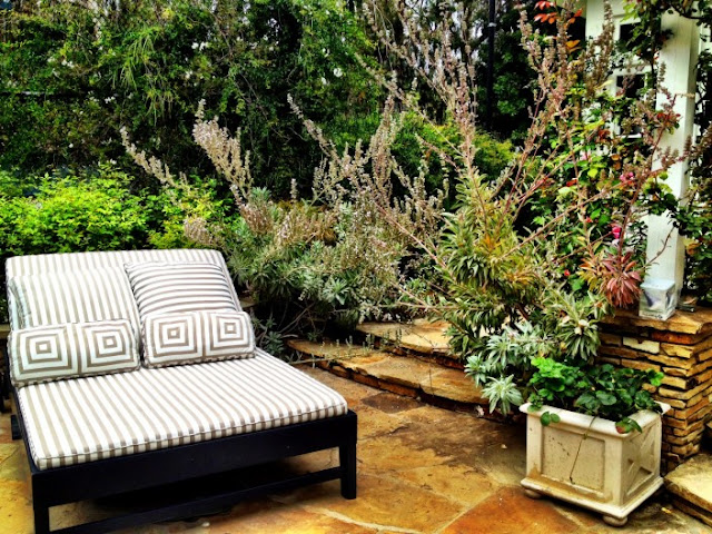 A double wide backyard garden chaise lounge chair surrounded by plants