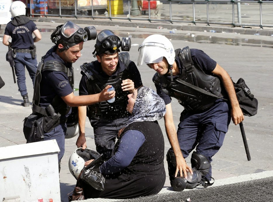 35 moments of violence that brought out incredible human compassion - riot police help a woman affected by tear gas